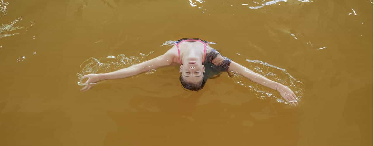 ragazza a dorso in piscina termale